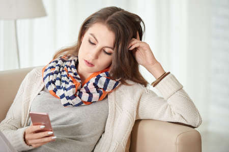 lady on phone: Woman sitting on sofa and reading message in her phone