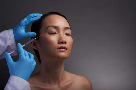 anesthetize: Chinese young woman having painful injections of hyaluronic acid