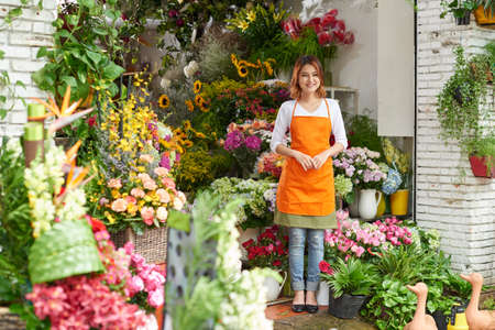 Young lovely florist working her flower shop Stock Photo