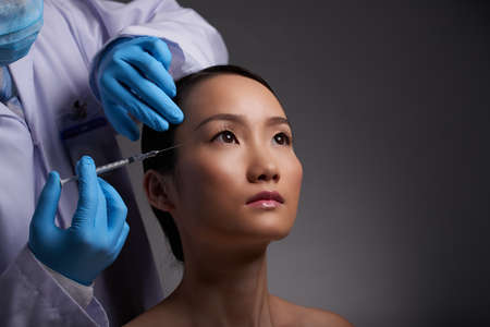anesthetize: Chinese young woman having beauty injection, isolated on grey Stock Photo