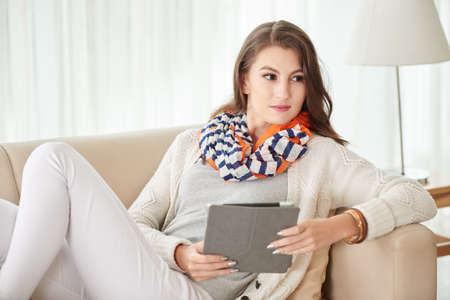Portrait of young womna with tablet computer lying on sofa Stock Photo