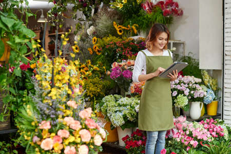 Flower shop owner working on tablet computer