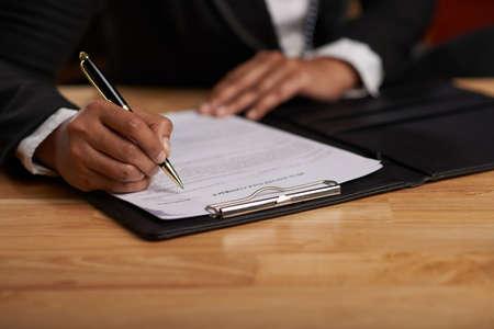 Manos de la dama de negocios que firman el contrato comercial