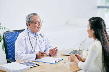 Vietnamese doctor consulting female patient in his office