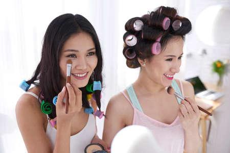 undereye: Young Vietnamese girl applying concealer under eyes