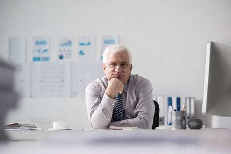 Pensive senior entrepreneur looking at camera when sitting at table