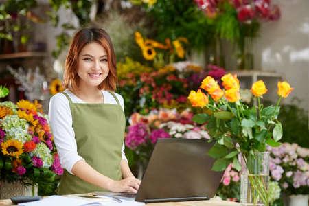 ラップトップに取り組んで元気なベトナム花屋の肖像画