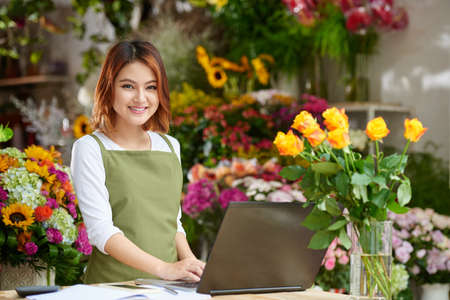 Portrait of cheerful Vietnamese florist working on laptop