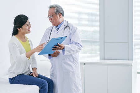 Asian doctor and patient discussing diagnosis or prescription
