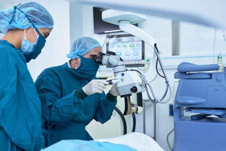 Twee professionele oogartsen die operatie aan ogen uitvoeren Stockfoto