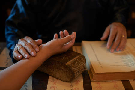 Asian traditional practitioner checking pulse of patient before treatment