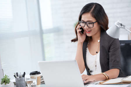 Smiling business lady talking on phone when working on laptop Stock Photo