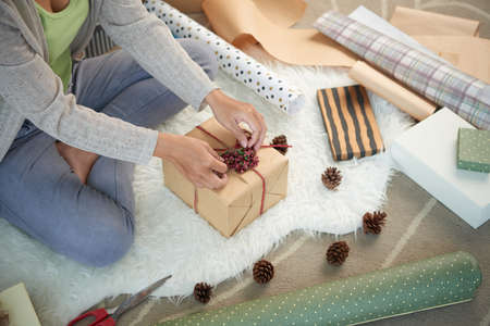Woman using berries and pine cones when decorating gift box