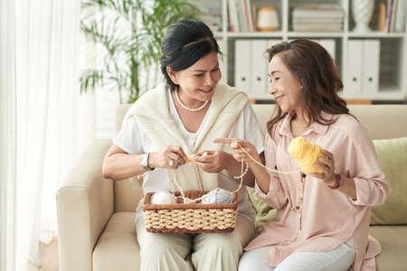 Senior Vietnamese female friends knitting together and chatting Reklamní fotografie