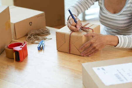 addressee: Close-up image of woman making note of giftbox