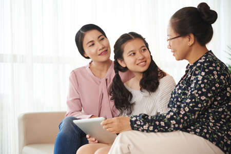 Senior Vietnamese woman telling stories to her daughter and granddaughter Stock Photo