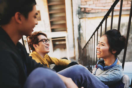 Profile view of attractive Vietnamese woman sitting on stairs and having fun with male friends, shabby wall of apartment house on background Stock Photo