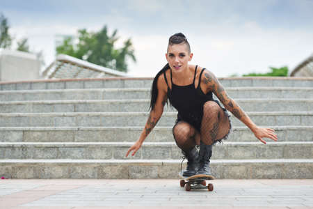 Stylish young woman with tattoo skateboarding in the city