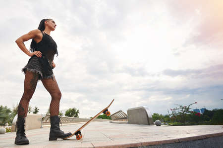 Stylish girl in shorts and fishnet stockings standing with one boot on the edge of skateboard Stock Photo