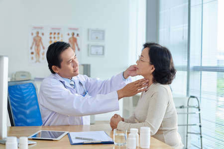 Concentrated middle-aged ENT specialist examining senior Asian patient while sitting at office desk, profile view Stock Photo