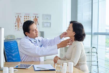 Geconcentreerde KNO-arts op middelbare leeftijd onderzoekt senior Aziatische patiënt zittend aan een bureau, profiel te bekijken