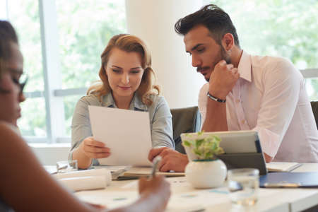 concentrate: Pretty blond-haired manager sharing ideas with her bearded colleague while having working meeting in spacious boardroom with panoramic windows Stock Photo