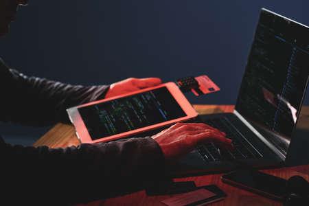 어둠 속에서 디지털 태블릿을 사용하여 노트북에 개인 데이터를 해킹하는 남성 손의 근접 촬영