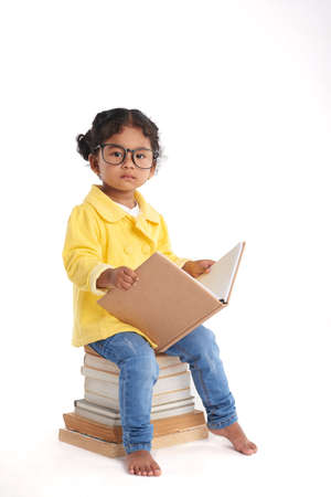 Full length portrait of pretty little girl looking at camera seriously while sitting on pile of books, isolated on white background Stock Photo