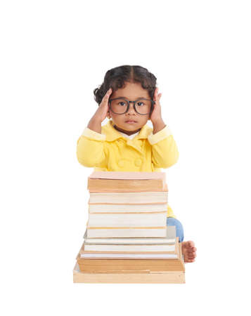 Smart toddler adjusting eyeglasses and posing for photography while sitting behind pile of shabby books, isolated on white background