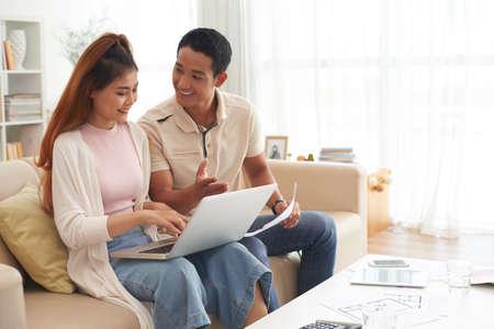 オンラインで新しい家を選択する若い家族 写真素材