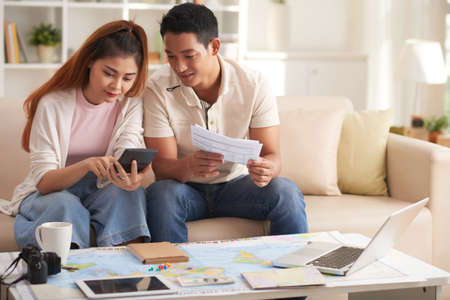 Young Asian Couple Planning Vacation Budget