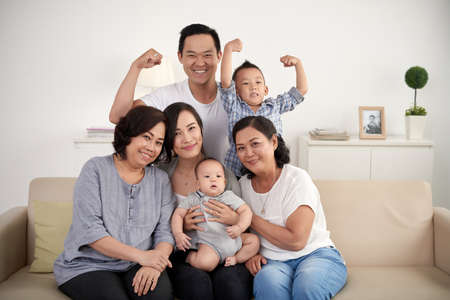 Portrait of big Asian family posing for photo at home: sitting on sofa, looking at camera and smiling happily