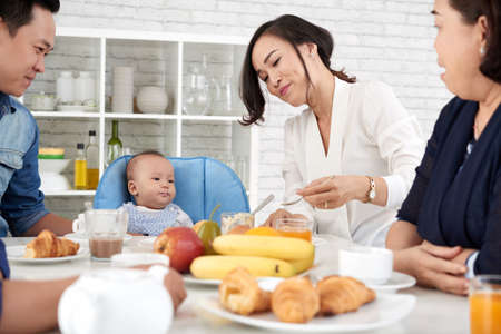 Portrait of big Asian family gathered at dinner table in the morning with cute baby boy