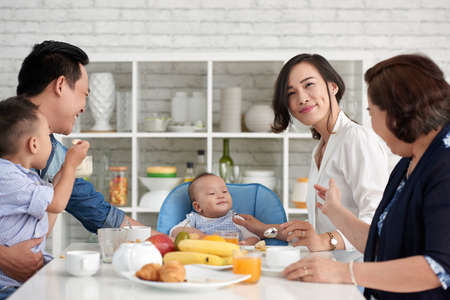 Portrait of young Asian woman sitting at breakfast table with baby boy and big family,  smiling happily to camera
