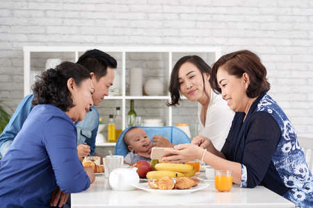 Portrait of big Asian family at breakfast, enjoying meal feeding cute baby boy showing him cartoons on smartphone  Happy Asian Family at Breakfast Table