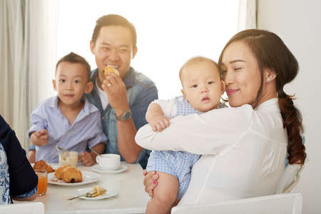 Happy Asian woman cuddling with cute baby boy at breakfast table with family on sunny morning