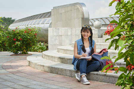 Full length portrait of joyful Asian student wearing jeans and shirt doing homework while sitting on stairs in university campus