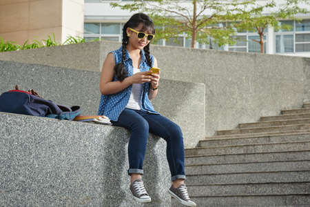 interval: Smiling young student sitting outdoors and texting with her friend on smartphone while having interval between lectures, full length portrait Stock Photo