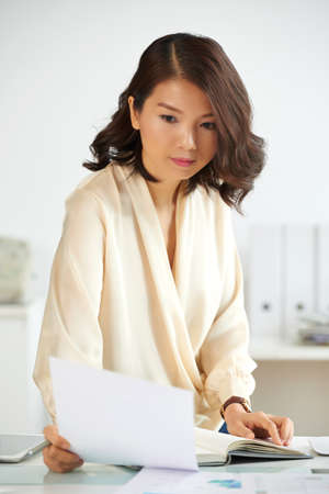 Portrait of young Asian businesswoman reading carefully document at office desk