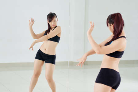 full length mirror: Attractive Asian woman with ponytail dancing in front of mirror in spacious dance hall, full-length portrait