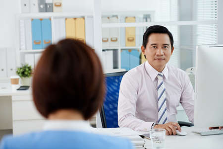 Portrait of unsmiling Asian business executive looking at camera when sitting at his table