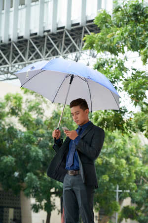 Young Businessman Standing with Umbrella in Street