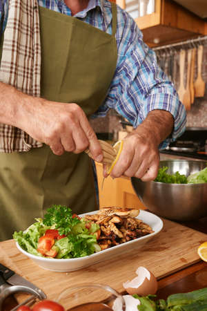 adding: Man preparing meal in the kitchen Stock Photo