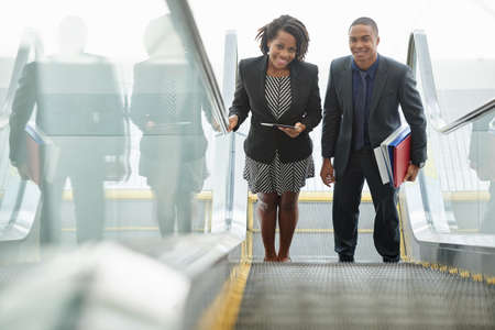 Businessman and businesswoman walking up the stairs