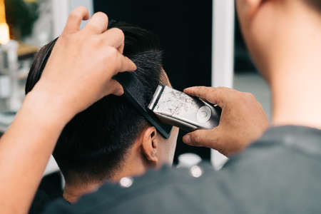 barbershop: Young man trimming hair at barbershop Stock Photo