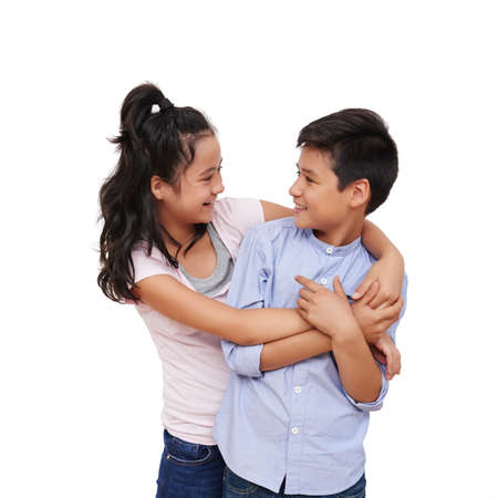 Studio shot of mixed-race brother and sister hugging and looking at each other Stock Photo