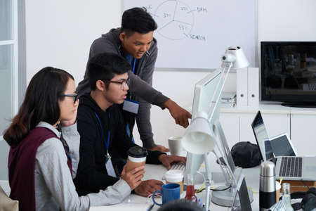 Young Asian programmers discussing code on computer screen