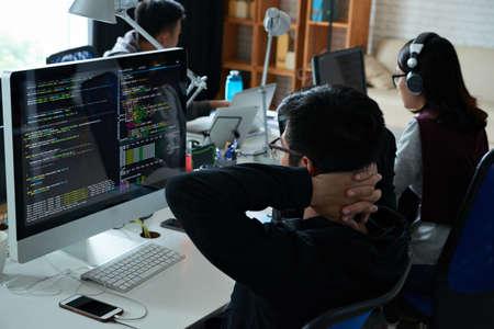 Peinzende programmeur die zijn code op het computerscherm bekijkt