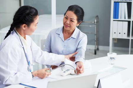 Doctor checking blood pressure of senior patient Foto de archivo