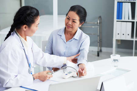 Doctor checking blood pressure of senior patient Banque d'images